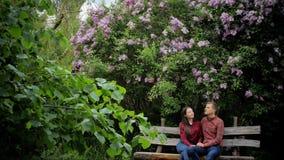 Romantische paarzitting op bank in park tijdens de zomer stock video