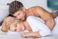 Romantische Partner, die auf Bett-Mode-Trieb liegen Stockfotografie