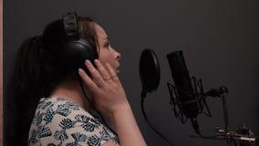 Romantische pop disco vrouwelijke zanger die beginnen te zingen Het meisje in hoofdtelefoons repeteert lied in professionele opna stock videobeelden