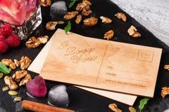 Romantische Postkarte Eine Draufsicht einer netten Karte, der Eisherzen, der rosa Beeren und der Walnüsse auf einem dunklen Hinte stockbild