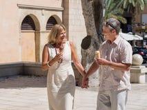 Romantische reife ältere Paare, die Eiscreme an einem heißen Tag genießen Lizenzfreie Stockfotos