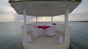 Romantische Reise, Bungalow mit Gläsern und Teller auf Tabelle am tropischen Strand gegen Wasser stock video footage