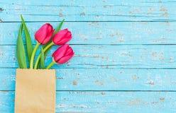 Romantische rode tulpenregeling in document zak op de lichtblauwe houten, mooie achtergrond van de de lentebloem met exemplaarrui stock foto
