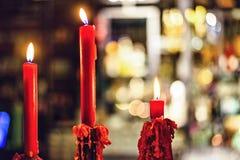 Romantische rote Kerzen, die im Nahaufnahmeschuß brennen stockbild