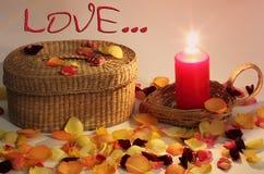 Romantische samenstelling Liefde De rieten mand en de gevlechte kaars en namen rond toe bloemblaadjes stock foto's