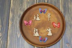 Romantische samenstelling op ceramische schotel Gestileerde houten cijfers van minnaars en kleurrijke siersatijnvlinders Donkere  royalty-vrije stock foto's