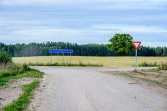 romantische Schotterstraße im Land unter blauem Himmel Lizenzfreies Stockfoto