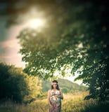 Romantische schwangere Frau draußen, unter den Bäumen Stockbild