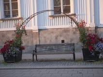 Romantische Stadtbank verziert mit schönen Blumen lizenzfreies stockbild