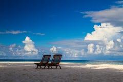 Romantische Strandlandschaft mit sunbeds auf den Malediven lizenzfreie stockfotografie