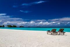 Romantische Strandlandschaft mit sunbeds auf den Malediven lizenzfreie stockfotos