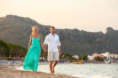 Romantische Strandpaare, die bei Sonnenuntergang gehen Stockbild