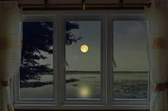 Romantische Vollmondnacht in der Fensteransicht stockbilder