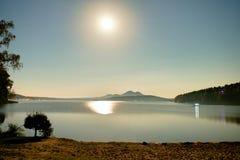 Romantische Vollmondnacht am See, strahlt ruhiger Wasserspiegel mit Mond aus Burh auf dem Hügel Stockfotografie