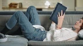 Romantische vrouw die op bus met fotoalbum ligt Glimlachend meisje die photobook kijken stock video