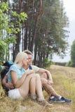 Romantische wandernde Paare, die bei der Entspannung im Wald weg schauen Stockbild