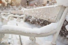 Romantische weiße Bank im Freien bedeckt mit Schnee Stockbilder