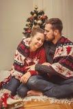 Romantische Weihnachtspaare zu Hause lizenzfreie stockbilder
