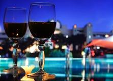 Romantische wijnglazen op een glaslijst bij hete nacht stock afbeeldingen