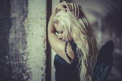 Romantischer blonder Engel, junge Frau mit schwarzen Flügeln, Herbst scen Stockfotografie