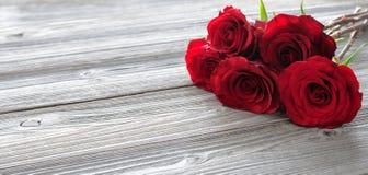 Romantischer Blumenrahmen mit roten Rosen auf hölzernem Hintergrund Lizenzfreie Stockbilder