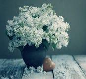 Romantischer Blumenstrauß des Frühlinges einer weißen Flieder in einem alten Vase der Weinlese und des Herzens mit Steinen Stockfoto