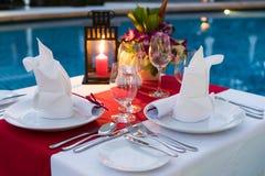 Romantischer Candlelit Abendtisch; Poolside mit Tabellen-Satz stockfoto
