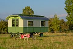 Romantischer hölzerner Wohnwagen mit Weinlesetabelle und Stühle in einer flämischen Wiese Lizenzfreies Stockbild
