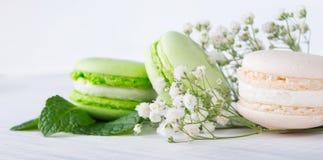 Romantischer Hintergrund Macaron mit Nachtisch und Blumen, Minze sahnig lizenzfreies stockbild