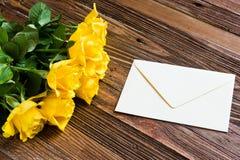 Romantischer Hintergrund mit den gelben Rosen, die auf einem Holztisch liegen stockbild