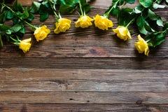 Romantischer Hintergrund mit den gelben Rosen, die auf einem Holztisch liegen stockbilder