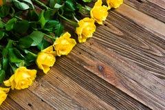 Romantischer Hintergrund mit den gelben Rosen, die auf einem Holztisch liegen stockfotografie