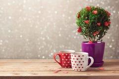 Romantischer Hintergrund mit Tasse Tee und Baumanlage mit Herzen auf Holztisch Glückliche junge küssende und celabrating Paare Lizenzfreie Stockfotos