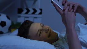 Romantischer Jugendlicher, der mit Freundin nachts, unter Verwendung des Smartphone im Bett plaudert stock video