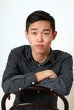 Romantischer junger asiatischer Mann, der auf einem Stuhl sitzt Stockfoto