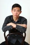 Romantischer junger asiatischer Mann, der auf einem Stuhl sitzt Stockfotos