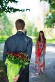 Romantischer junger Mann, der einen Blumenstrauß der roten Rosen zu seinem girlfrie gibt Lizenzfreie Stockfotografie