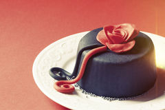 Romantischer Kuchen auf einer Platte mit Dekorationen Rose oben Schattiert roten Hintergrund Lizenzfreies Stockbild