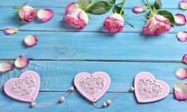 Romantischer Liebeshintergrund mit rosa Rosen und Herzen Stockbilder