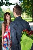 Romantischer Mann, der seiner Freundin einen Blumenstrauß der roten Rosen gibt Lizenzfreie Stockfotos