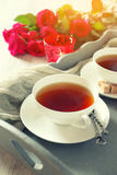 Romantischer Morgentee für zwei mit Kerzen und roten Rosen Stockbild