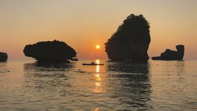 Romantischer Sonnenuntergang an den Küsten-Kalksteinfelsensteinen des Indischen Ozeans steigen über die Leute im Kajak, Kräuselun stock footage