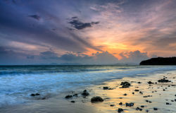 Romantischer Sonnenuntergang an einem felsigen Strand lizenzfreie stockfotografie