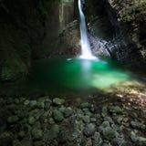 Romantischer Wasserfall, der eine Gletscherspalte durchfließt, um See zu grünen lizenzfreie stockfotos