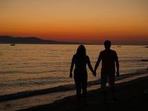 Romantischer Weg auf dem Strand am Sonnenuntergang. Stockfotos