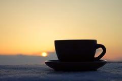 Romantischer Tasse Kaffee oder Tee in den Strahlen des Sonnenuntergangs Lizenzfreie Stockfotos