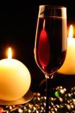 Romantisches Abendessen - Glas Rotwein und Kerzen Stockfotos