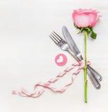Romantisches Abendtischgedeck mit Gabel, Messer, Rosarose und Herzen auf weißem hölzernem Hintergrund, Draufsicht Rot stieg auf w Stockfoto