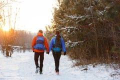 Romantisches Bild von der Rückseite des Mannes und der Frau mit Rucksäcken im Winter Lizenzfreie Stockbilder