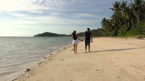 Romantisches Coulpe, das auf den Strand bei Sonnenuntergang geht stock footage